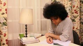 ung man som studerar och skriver på boken stock video