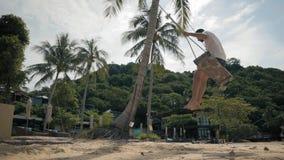 Ung man som svänger på gungorna på stranden på bakgrunden av ett hotell stock video