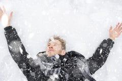 Ung man som täckas i snö som ligger på jordningen i snöfall z royaltyfri foto