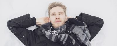 Ung man som täckas i snö som ligger på jordningen i snöfall z royaltyfri bild
