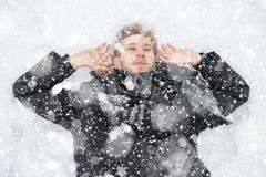Ung man som täckas i snö som ligger på jordningen i snöfall z royaltyfri fotografi