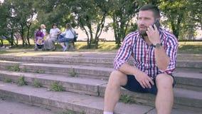 Ung man som talar av smartphonen som sitter på trappa glidareskott arkivfilmer