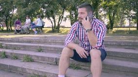 Ung man som talar av smartphonen som sitter på trappa glidareskott stock video