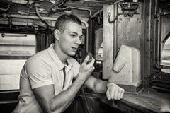 Ung man som talar in i radio i drevmotor Arkivbilder