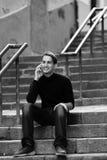 Ung man som talar på mobil, medan sitta på trappan utomhus royaltyfri foto