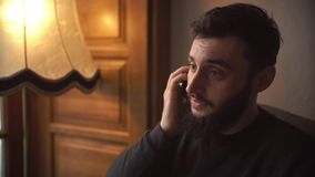 Ung man som talar på mobiltelefonen i hemtrevligt kafé lager videofilmer