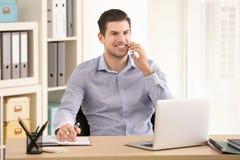 Ung man som talar på mobiltelefonen, medan arbeta royaltyfri bild