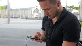 Ung man som talar på mobiltelefonen på en bänk i staden lager videofilmer