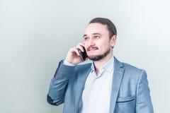 Ung man som talar på telefonen i ett grov bomullstvillomslag på grå bakgrund Arkivfoton