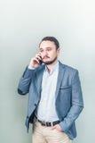Ung man som talar på telefonen i ett grov bomullstvillomslag på grå bakgrund Arkivfoto