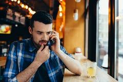 Ung man som talar på telefonen i kafé arkivfoto