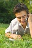 Ung man som talar på telefonen i parken Royaltyfri Bild