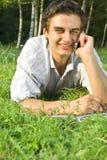 Ung man som talar på telefonen i parken Royaltyfri Foto