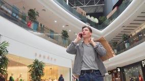 Ung man som talar på telefonen på shoppinggallerian stock video