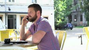 Ung man som talar vid smartphonen i kafét, glidareskott, rätt lager videofilmer