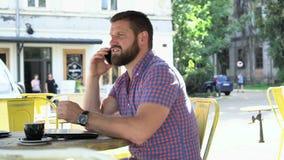 Ung man som talar vid smartphonen i kafét, glidareskott som lämnas lager videofilmer