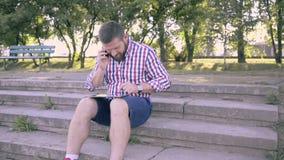 Ung man som talar vid smartphonen och bläddrar minnestavlan Glidare- och pannaskott stock video