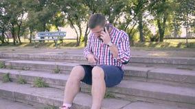 Ung man som talar vid smartphonen och bläddrar minnestavlan Glidare- och pannaskott som är högert stock video