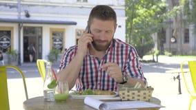 Ung man som talar vid smartphonen, under lunch lager videofilmer