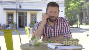 Ung man som talar vid smartphonen, under lunch-, glidare- och pannaskott lager videofilmer