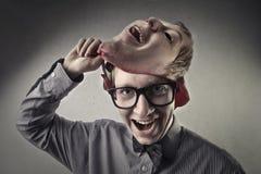 Ung man som tar av en maskering arkivfoto
