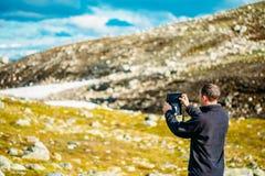 Ung man som tar bilder av det norska berget Arkivbild
