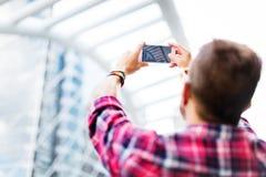 Ung man som tar det fotoSmartphone begreppet arkivfoto