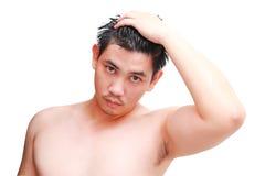 Ung man som tar en dusch och ett anseende under flödande vatten i badrum Royaltyfria Foton