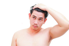 Ung man som tar en dusch och ett anseende under flödande vatten i badrum Arkivbild