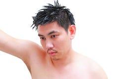Ung man som tar en dusch och ett anseende under flödande vatten i badrum Arkivfoton