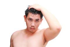 Ung man som tar en dusch och ett anseende under flödande vatten i badrum Royaltyfri Fotografi