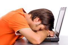 Ung man som tar en ta sig en tupplur på hans bärbar dator royaltyfria bilder