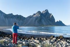 Ung man som tar ett foto till det Vestrahorn berget i den Stokksnes halvön, Island royaltyfri foto