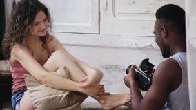 Ung man som tar fotoet av kvinnan på gammal flyttning-film kamera Härlig flicka, i att posera för pyjamas som gör upp hår arkivfilmer