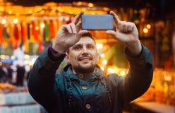 Ung man som tar fotoet med telefonen på gatan som dekoreras med färgrika flaggor royaltyfria foton