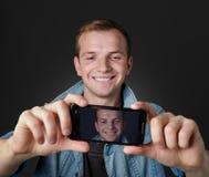 Ung man som tas ett självfoto med hans mobiltelefon arkivbild