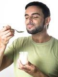 Ung man som äter yoghurt Arkivbilder