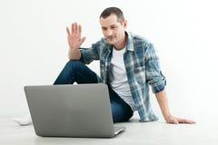 Ung man som till varandra talar via online-video pratstund Stilig man som använder bärbara datorn för affär och underhållning Royaltyfria Foton