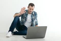 Ung man som till varandra talar via online-video pratstund Stilig man som använder bärbara datorn för affär och underhållning Arkivfoton