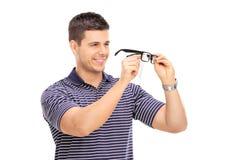 Ung man som torkar hans exponeringsglas Arkivbilder
