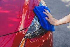 Ung man som tvättar och torkar en bil i det utomhus- Arkivbild