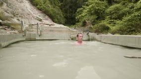 Ung man som tycker om det termiska badet i utomhus- brunnsortsemesterort Stilig man som badar i mineralvattenpöl Naturligt brunns stock video