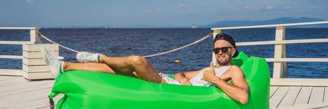 Ung man som tycker om fritid som ligger på luftsoffan Lamzac, nära havsBANRET, LÅNGT FORMAT royaltyfri foto