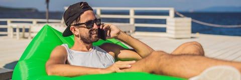 Ung man som tycker om fritid som ligger på luftsoffan Lamzac, nära havsBANRET, LÅNGT FORMAT royaltyfria foton
