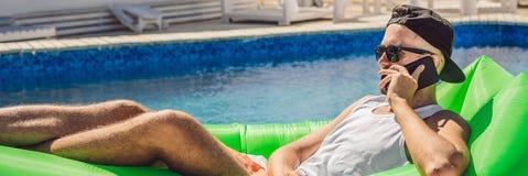 Ung man som tycker om fritid som ligger på luftsoffan Lamzac, nära pölBANRET, LÅNGT FORMAT royaltyfria foton