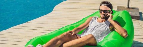 Ung man som tycker om fritid som ligger på luftsoffan Lamzac, nära pölBANRET, LÅNGT FORMAT arkivbild