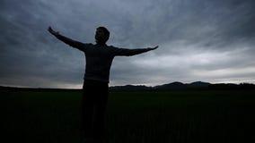 Ung man som tycker om liv under molnig aftonhimmel lager videofilmer