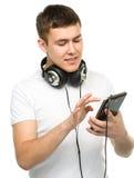 Ung man som tycker om musik genom att använda hörlurar Royaltyfri Bild