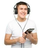 Ung man som tycker om musik genom att använda hörlurar Arkivbilder
