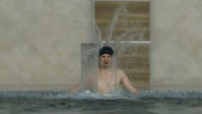 Ung man som tycker om pölbrunnsortdag i avslappnande semestersemesterort Hydromassagen för hals smärtar Koppla av under vattenstr lager videofilmer